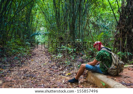 Travelling man sitting in the bamboo forest. Phuket