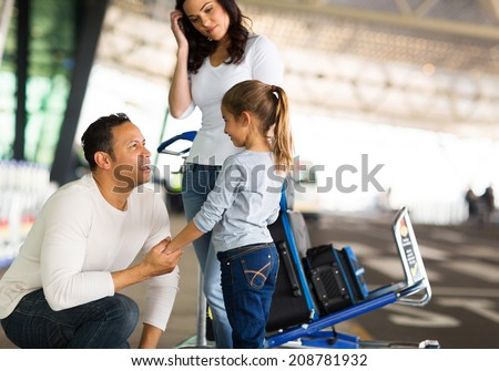 travelling man talking to her daughter at airport before departure - stock photo