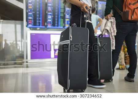 Travelling suitcase against flight information board on background. Concept of travel by airplane - stock photo