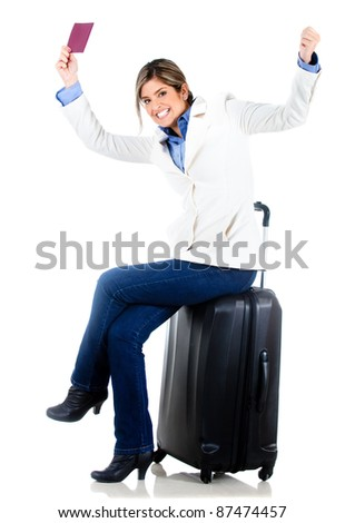 Travelling woman sitting on her bag and holding a passport - isolated over white background
