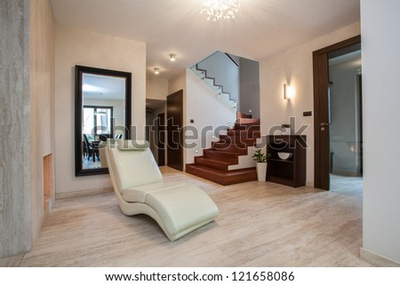 Travertine house: hallway with comfortable armchair - stock photo