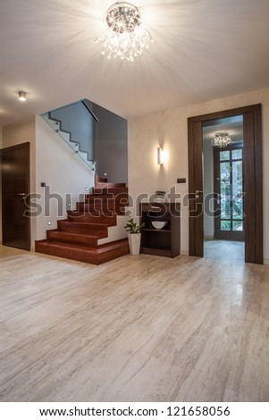 Travertine house: wooden stairs and glass entrance - stock photo