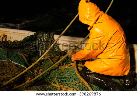 Trawl master repairs fishing trawl. Night time. - stock photo