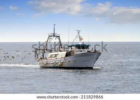 Trawler fishing boat working along the coast of Alicante in Spain - stock photo