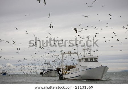trawler surrounded by seagulls under covered sky - stock photo