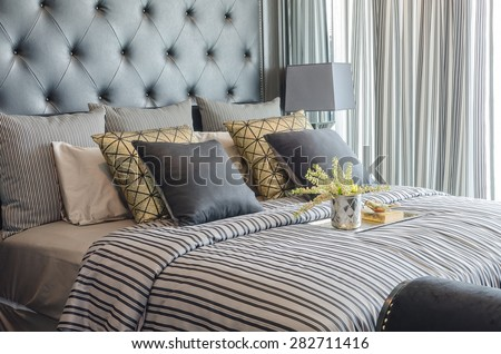 tray of book with vase of  plant on bed in luxury black bedroom at home - stock photo