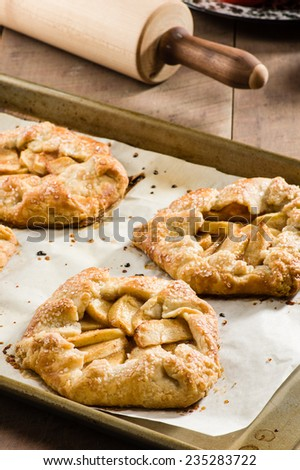 Tray of freshly baked apple tarts with a rolling pin - stock photo