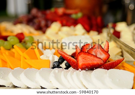 Tray of sliced cheeses and fruits, selective focus on the sliced strawberries - stock photo