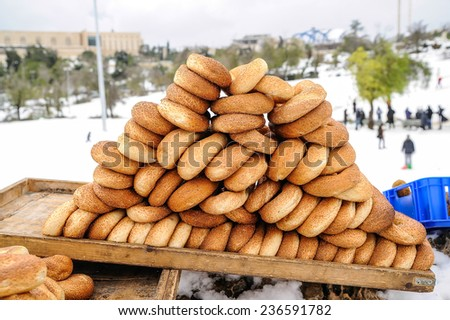 Tray with bagels in Jerusalem park covered in snow - stock photo