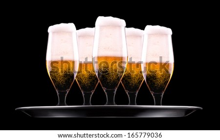 tray with Beer into glass on a black - stock photo