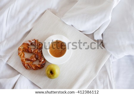 Tray with breakfast on a bed. Sweet pretzel, Cup of coffee and Apple. Top view
