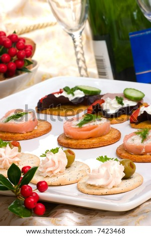Tray with fresh sandwiches on holiday table with Christmas decoration, glasses and bottle of champagne - stock photo