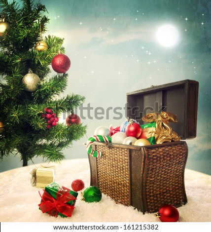 Treasure box filled with Christmas ornaments and presents on snow with Christmas tree - stock photo