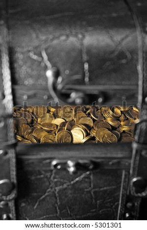 Treasure chest in black and white, with gold coins peaking through from inside - stock photo