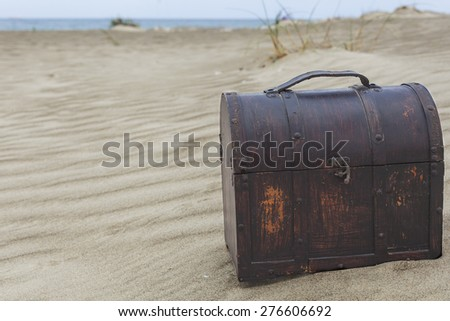 Treasure chest in sand dunes on a beach - stock photo