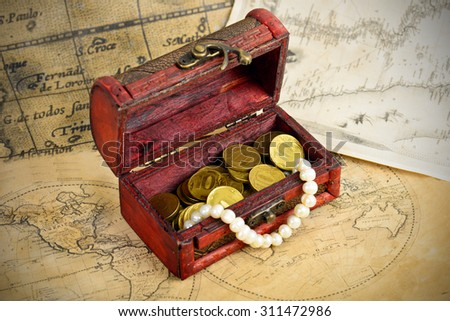 Treasure chest with coins on old adventure maps - stock photo