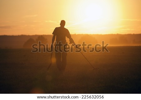 Treasure hunter with Metal detector in the field on the sunset - stock photo