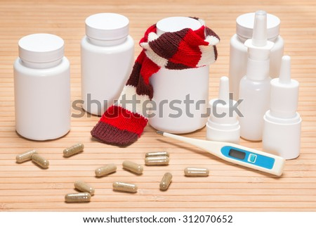 Treatment of colds and flu concept. Jar of pills, tied with knitted scarf, surrounded by jars of medicines, scattered capsules, electronic thermometer, nasal sprays