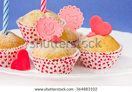 Treats for Valentine's day. Cupcakes in paper decorated with hearts of sugar paste - stock photo