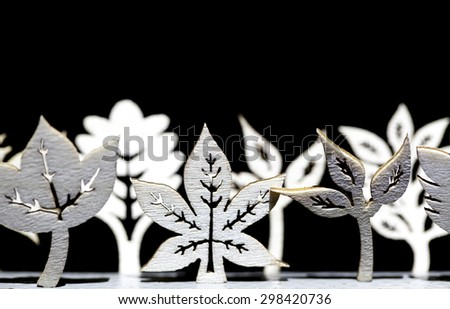 Tree and leaf wooden shapes on a black background - stock photo