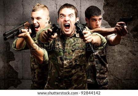 Tree armed soldiers with gas mask and rifles against a grunge bricks wall - stock photo
