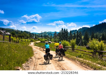 Tree bicyclist in sunny mountain landscape. Green grass, trees and blue sky  - stock photo