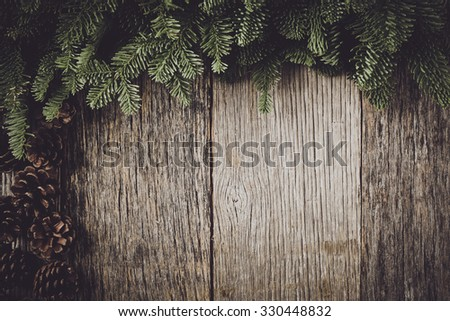 Tree branch on rustic wooden background  with pine cones - stock photo