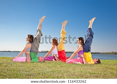 Tree couple , man and woman practice Yoga asana on lake banch - stock photo