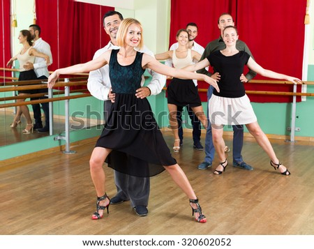 Tree elegant  positive  couples dancing waltz in dancing-class - stock photo