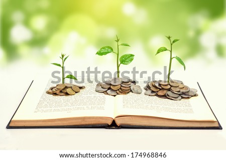 "tree growing from books with coins / A big open book with coins and tree. ""Reading makes you richer"" concept. - stock photo"
