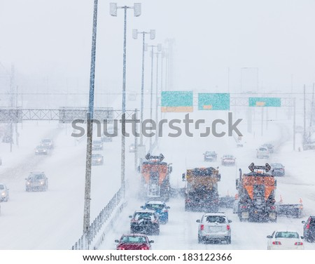 Tree Lined-up Snowplows Removing the Snow the Highway on a Cold Snowy Winter Day - stock photo