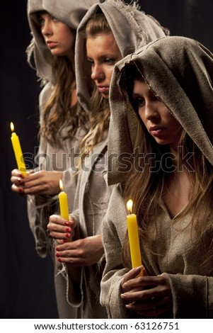 Tree nuns praying with candles in their hands - stock photo