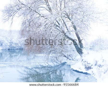 tree on the bank of the river in snowfall - stock photo