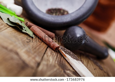 Tree spoons with spices and a bundle of herbs, mortar and pestle  - stock photo