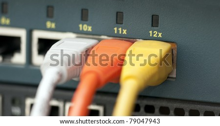 Tree UTP cables plugged in a switch - stock photo