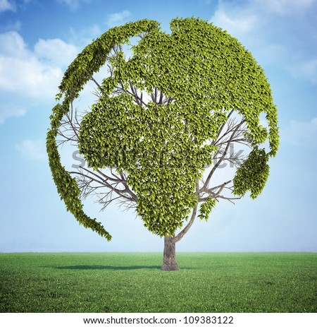 Tree with the leafs forming the world map on a meadow - stock photo