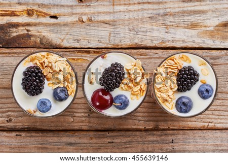 Tree yogurt desserts with berries and muesli in row. - stock photo