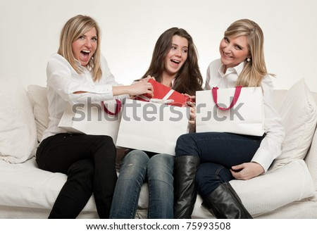 Tree young female friends sitting on a sofa with presents - stock photo