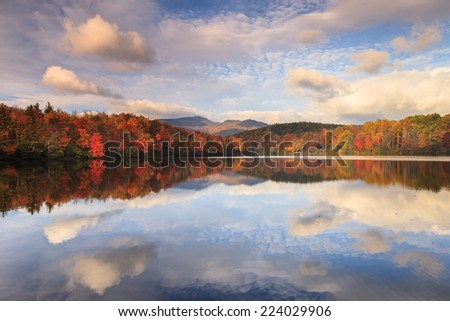 Trees along Julian Price Lake displaying and reflecting autumn colors under the morning sun, blue sky and white clouds right off the Blue Ridge Parkway in North Carolina.