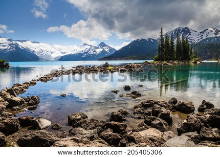 Trees and Mountains reflected in blue and green Garibaldi Lake  - stock photo