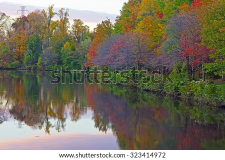 Trees and reflections around a city pond in Falls Church, Virginia, USA. Autumn colors at sunset in urban area. - stock photo