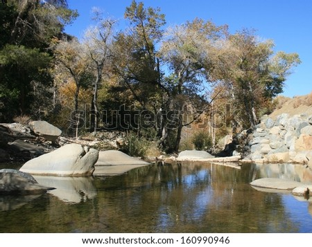 Trees and rocks on the bank of a clear stream in the high desert, California - stock photo