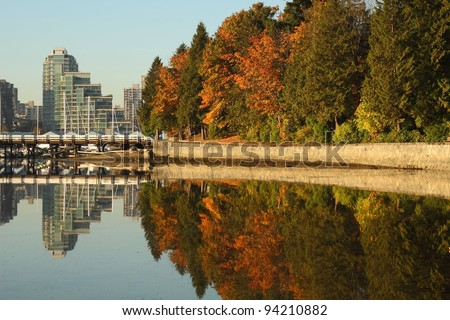 Trees and the pedestrian seawall of Stanley Park reflected in the calm waters of Coal Harbor. Vancouver, British Columbia, Canada. - stock photo