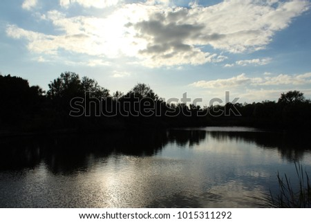 Trees around a lake with clouds and water reflection