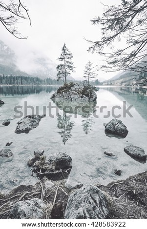 Trees growing on small island in middle of stunning mountain lake Hintersee, Ramsau, Germany. Vertical toned landscape of from Berchtesgaden National Park, German Bavarian Alps - stock photo