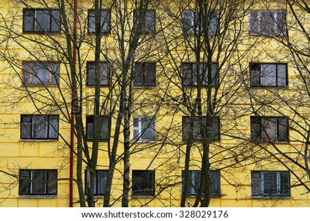 Trees in front of yellow house. Architectural background. - stock photo