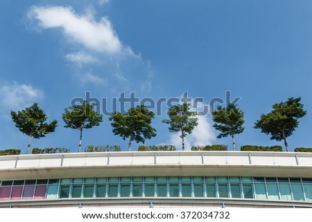 Trees on the roof of modern architecture office building with blue sky background. - stock photo