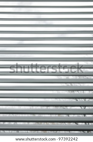 Trees seen through semi-closed metallic blinds on a window. - stock photo