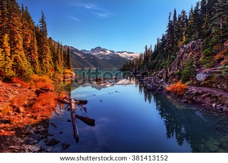 Trees surrounding the placid lake, snowcapped mountains, and sun illuminating the landscape - stock photo