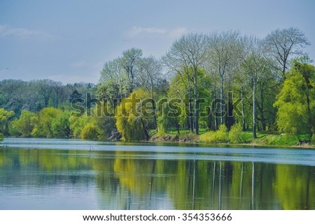 Trees with spring foliage on the bank of the river on a sunny day - stock photo